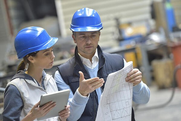 Engineers in mechanical factory reading instructions-2